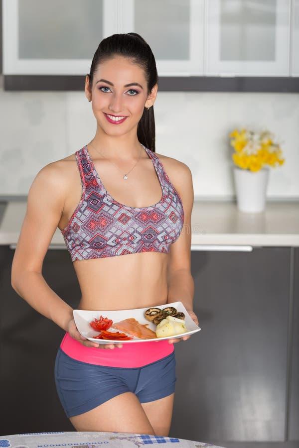 Geeignete Frau der Junge in der Küche, gesunde Mahlzeit vorbereitend stockbild