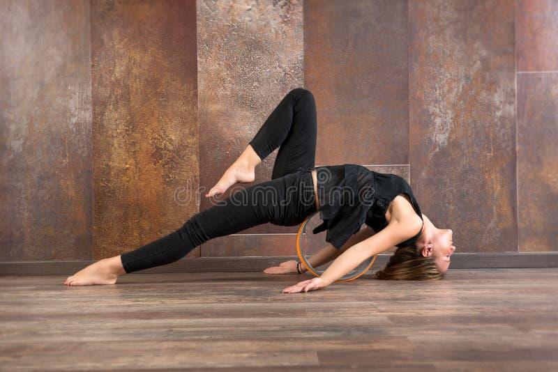 Geeignete Frau der Junge, die matsyasana Yogahaltung tut lizenzfreies stockfoto