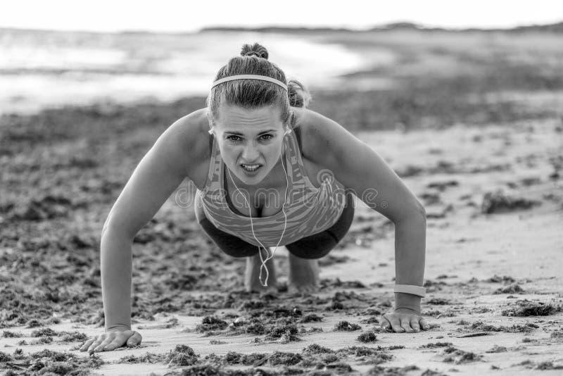 Geeignete Frau der Junge im Sport übersetzen auf der Küste, die Liegestütze tut stockfotografie