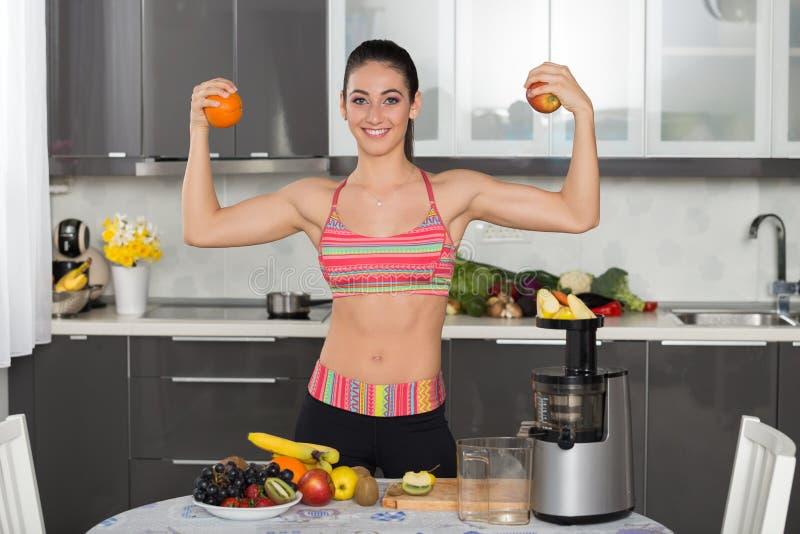 Geeignete Frau der Junge mit Früchten, in der Küche stockfotos