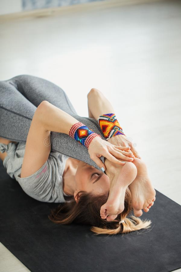 Geeignete Frau, die Aufwärmen, Yogaübung ausdehnend auf Matte tut stockfotografie
