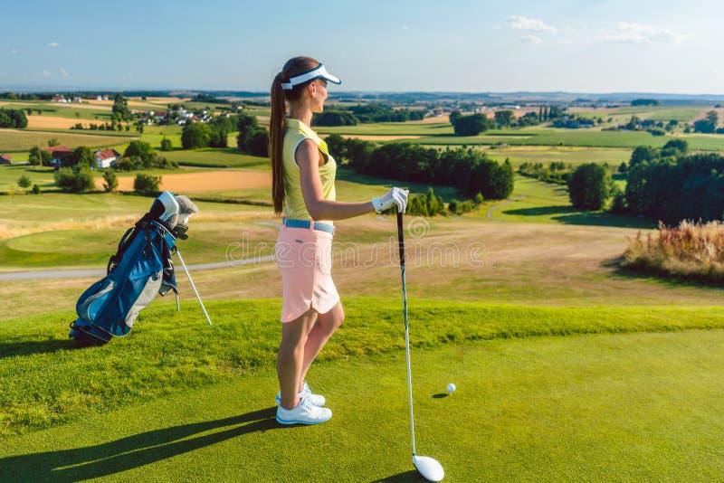 Geeignete Frau, die den Horizont auf dem gr?nen Gras eines Golfplatzes betrachtet stockfotografie