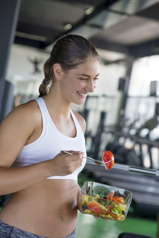 Geeignete Frau, die gesunden Salat nach Training isst lizenzfreie stockfotos