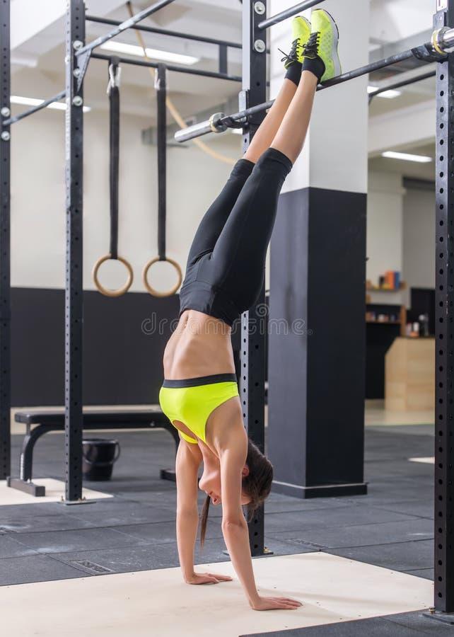 Geeignete Frau, die Handstand Athleten steht auf Handkonzeptbalancen-Sporteignung tut stockfotografie