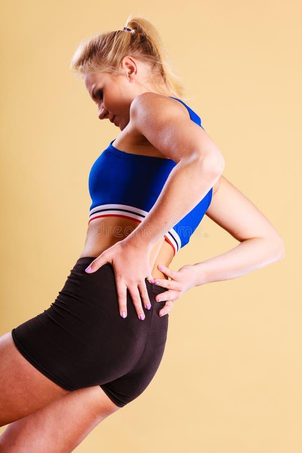 Geeignete Frau, die unter Rückenschmerzen leidet lizenzfreie stockfotografie