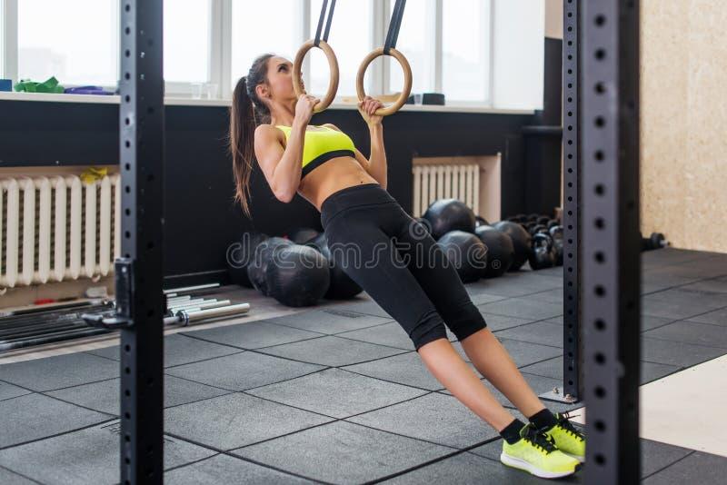 Geeignete Frau, die ZugUPS mit gymnastischen Ringen in der Turnhalle, junge Frau ausarbeitet Bizeps, Trizeps, ABS tut stockbilder