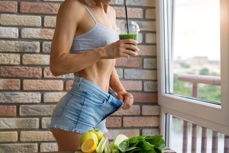 Geeignete Frau trinkender grüner Detox Gemüsesmoothie rohe Lebensmitteldiät stockfotos