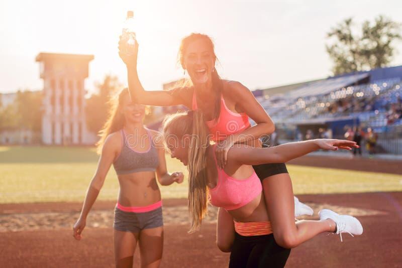 Geeignete Frauen der Gruppe, welche piggyback Fahrt die glücklichen jungen Freunde genießen einen Tag am Stadion geben stockfotos