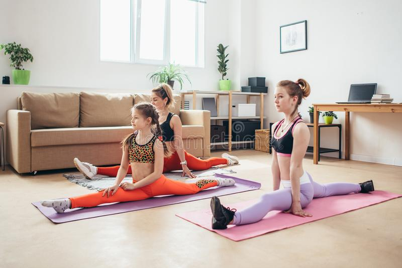 Geeignete Frauen, die Spalten tun Mutter und Töchter, die, Beine ausdehnend trainieren stockfoto
