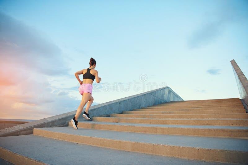 Geeignete gesunde junge Frau, die herauf Treppe rüttelt lizenzfreie stockfotos