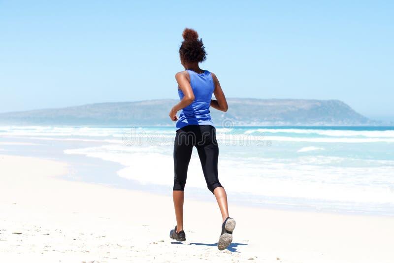 Geeignete junge Frau, die auf dem Strand läuft lizenzfreies stockbild