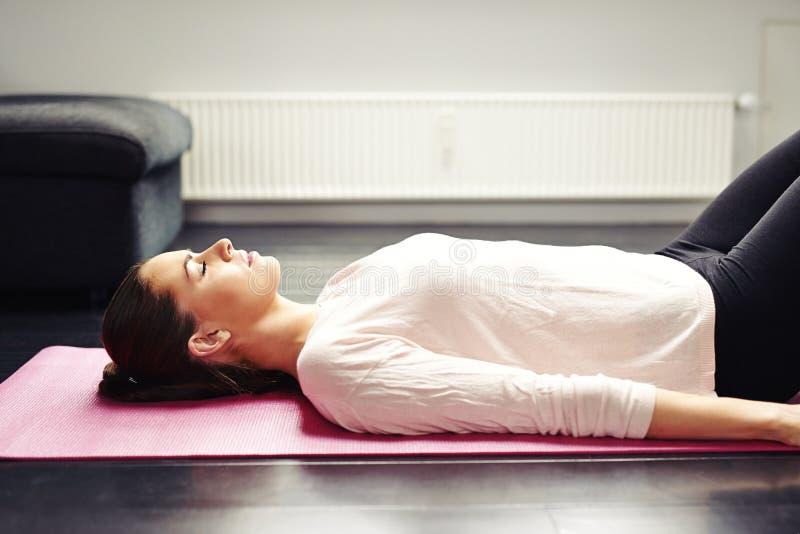 Geeignete junge Frau, die auf Yogamatte sich entspannt lizenzfreie stockfotos