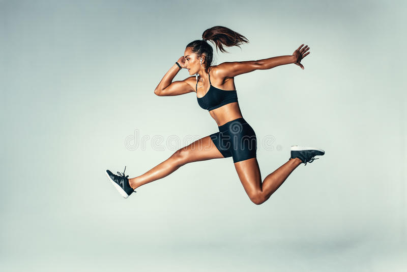 Geeignete junge Frau, die in einer Luft springt stockfotografie