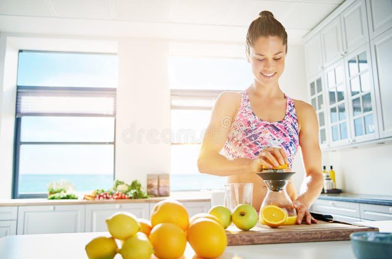 Geeignete junge Frau, die gesunden Fruchtsaft zubereitet stockfotos