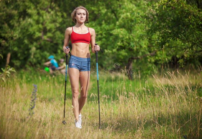 Geeignete junge Frau, die mit nordischen Wanderstöcken wandert stockbild
