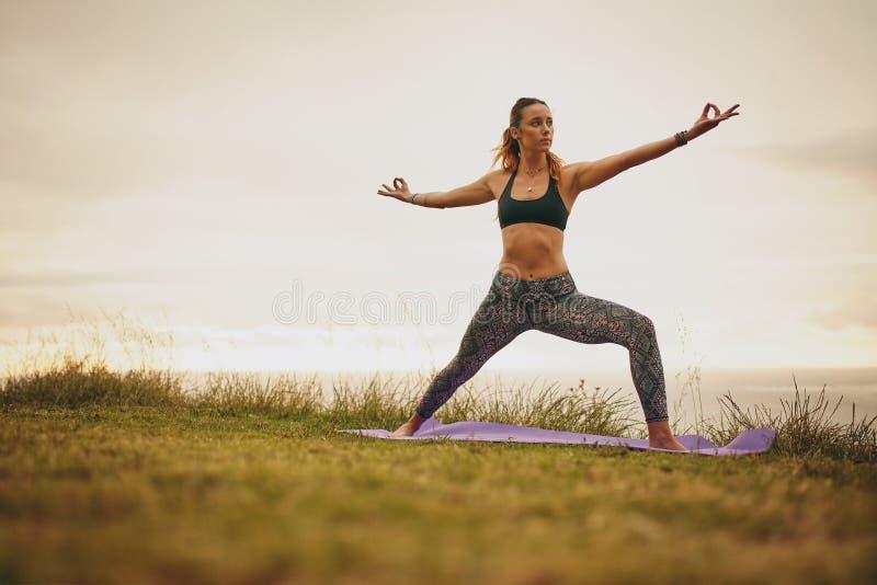 Geeignete junge Frau, die Yoga auf Klippe tut lizenzfreie stockbilder