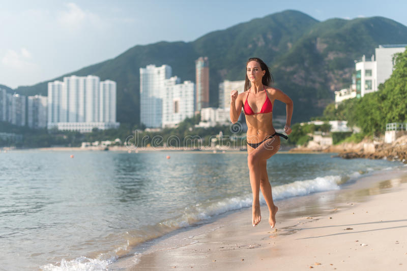 Geeignete junge Frau im Bikini mit dem sportlichen muskulösen sexy Körper, der auf Küste gegen Berge und Hochhäuser rüttelt lizenzfreies stockbild