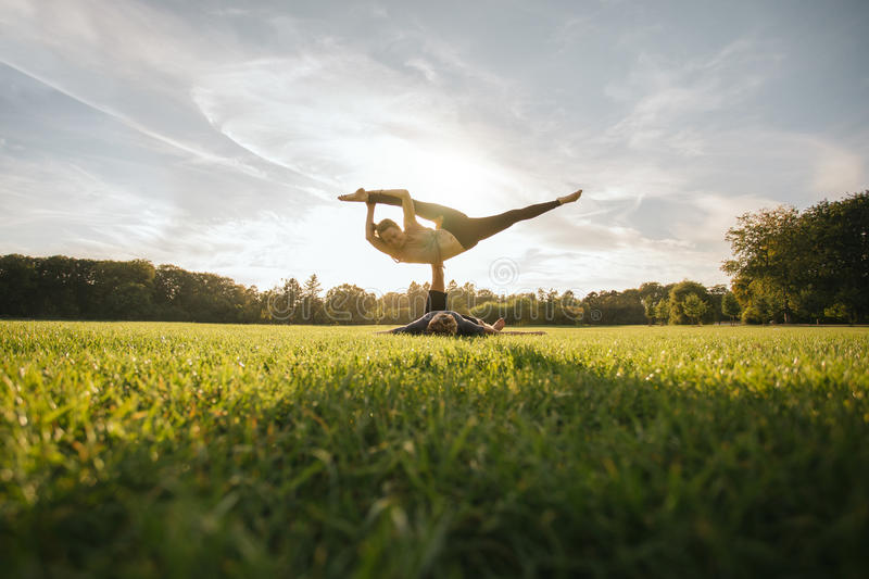 Geeignete junge Paare, die acro Yoga tun stockbild
