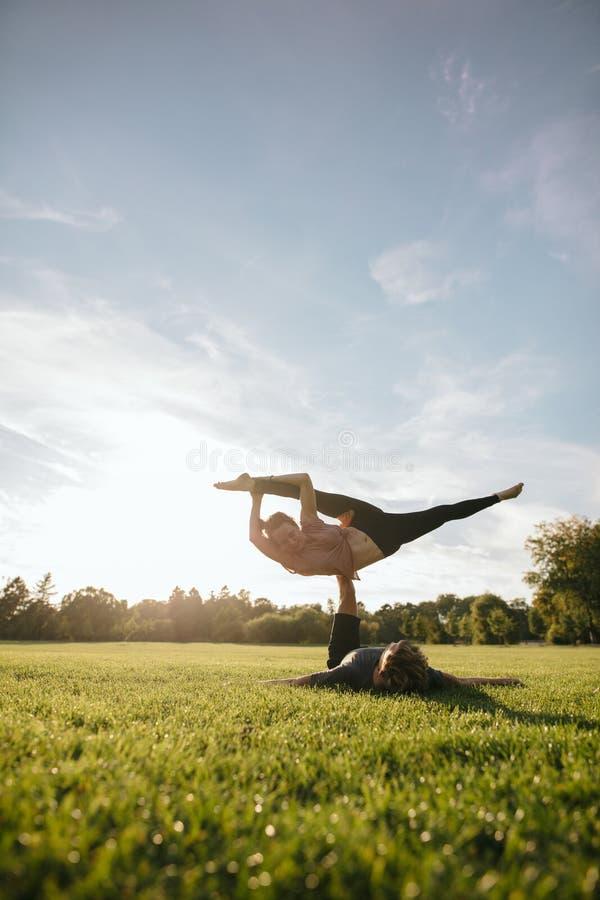 Geeignete junge Paare, die akrobatisches Yoga tun stockbilder