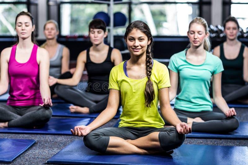 Geeignete lächelnde Gruppe, die Yoga tut stockfotografie