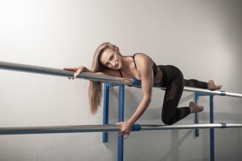 Geeignete M?dchen, die Beintraining vorbereiten Das Bein, welches die ?bungseignungsfrau tut Aufw?rmen, Kniesehnenmuskeln ausdehn lizenzfreie stockfotografie