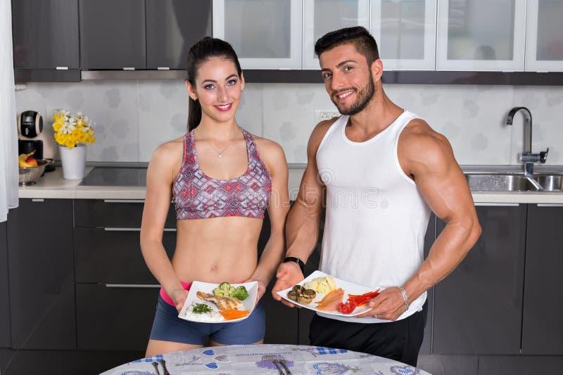 Geeignete Paare in der Küche, Halteplatten des Lebensmittels lizenzfreie stockfotos