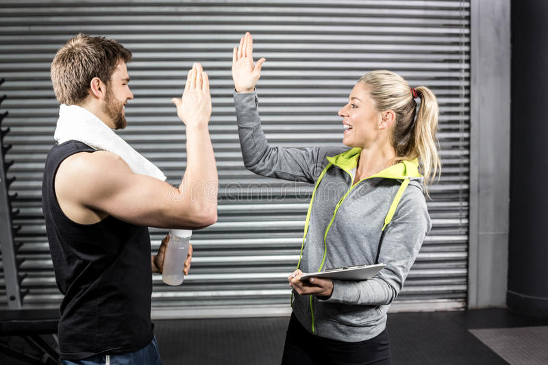 Geeignete Paare hohes Fiving in crossfit Turnhalle stockfotos
