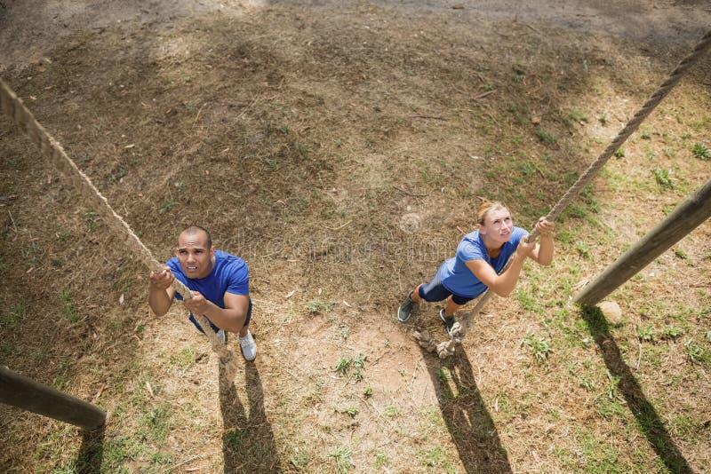Geeignete Person, die unten das Seil während des Hindernislaufs klettert lizenzfreies stockfoto