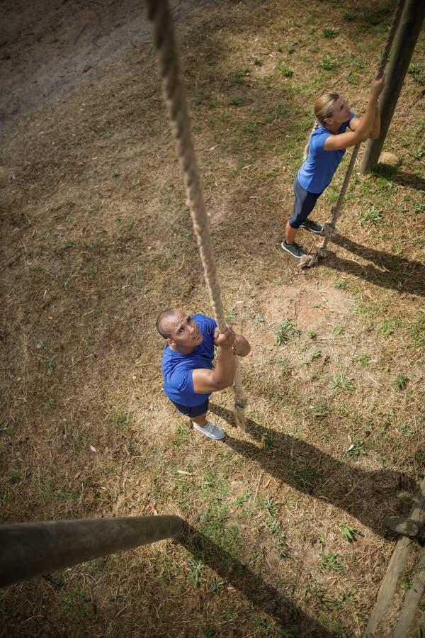 Geeignete Person, die unten das Seil während des Hindernislaufs klettert stockfoto