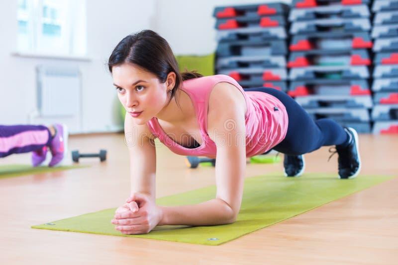 Geeignete sportive Frau, welche die Plankenkernübung zurück ausbilden und Pressemuskelkonzeptturnhallensportsportlereignungstrain stockfotografie