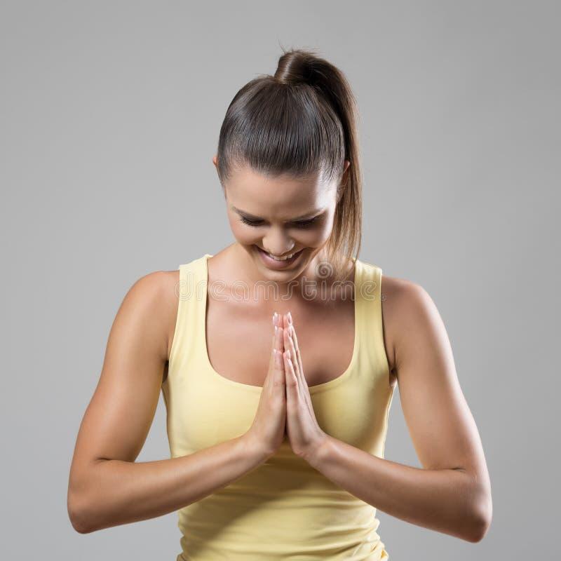 Geeignete sportliche Frau in Gebet namaste Handzeichen unten lächelnd und schauend lizenzfreie stockbilder