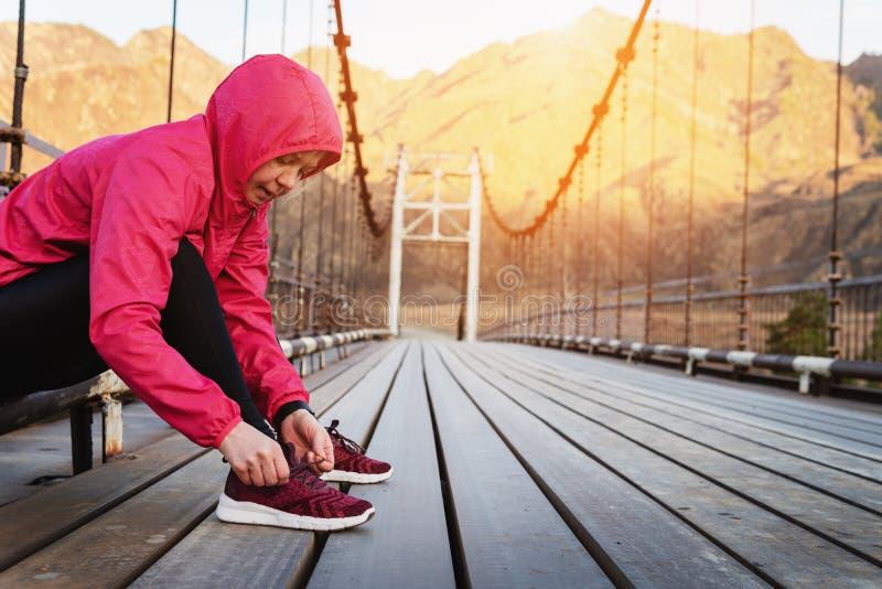Geeignete und sportliche Frau, die ihre Spitzee vor einem Lauf bindet lizenzfreies stockfoto