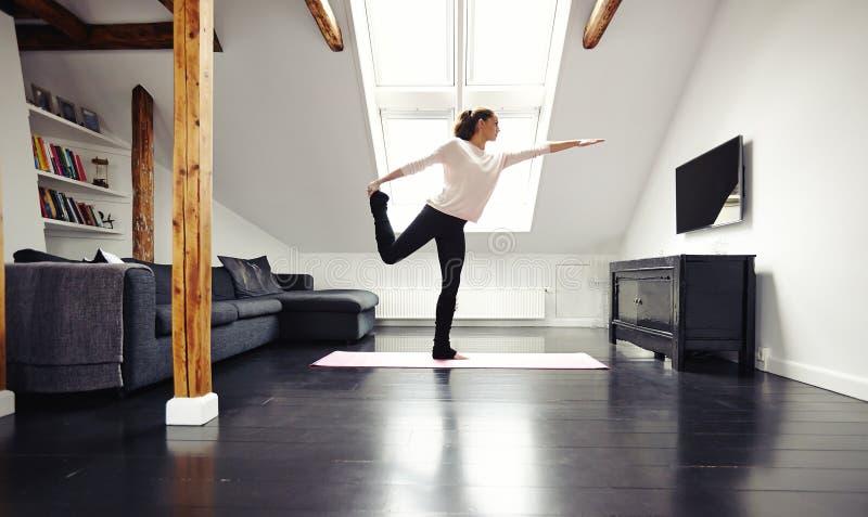 Geeignete Yoga junger Dame übende zu Hause - Kriegershaltung stockfotografie