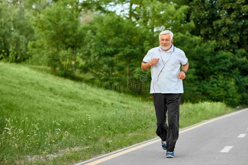Geeigneter alter Mann, der auf Rennbahn im grünen Park läuft lizenzfreie stockfotos