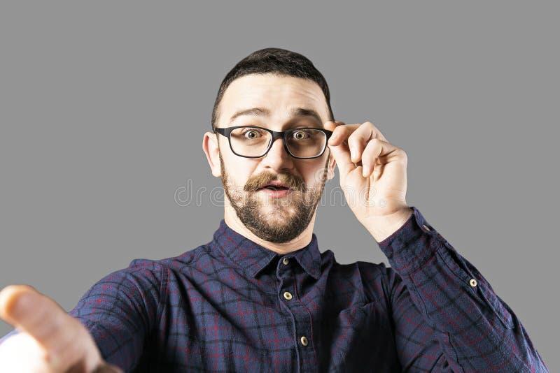Geeigneter junger Mann, der über grauem Hintergrund aufwirft lizenzfreie stockfotografie