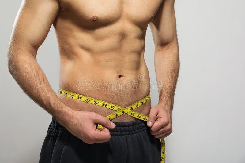 Geeigneter junger Mann, der seine muskulöse Taille misst lizenzfreie stockbilder