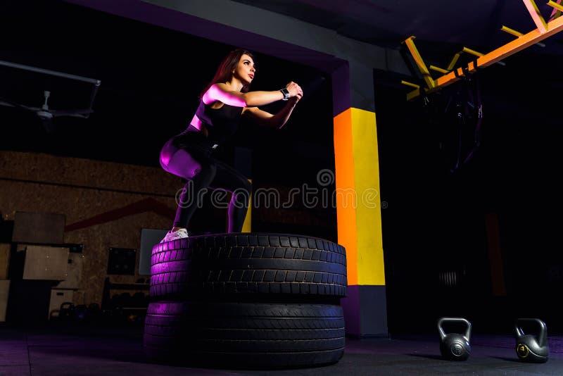Geeigneter Kasten der jungen Frau, der auf Reifen springt stockbild