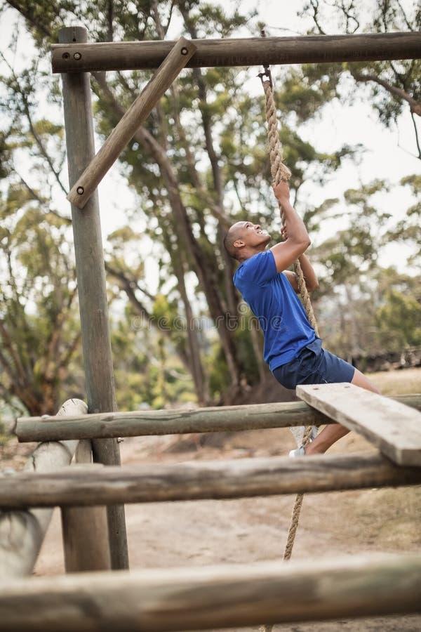 Geeigneter Mann, der ein Seil während des Hindernislaufs klettert stockbilder