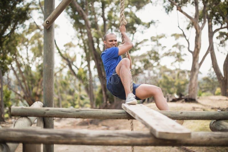 Geeigneter Mann, der ein Seil während des Hindernislaufs klettert stockfoto