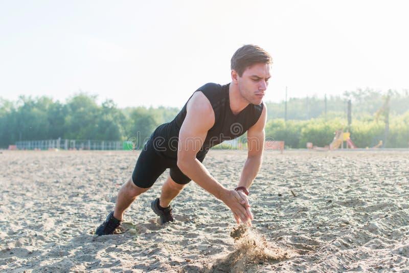 Geeigneter Mann, der klatschendes StoßUPS während des Schulungsübungstrainings auf Strand im Sommer tut lizenzfreie stockfotografie