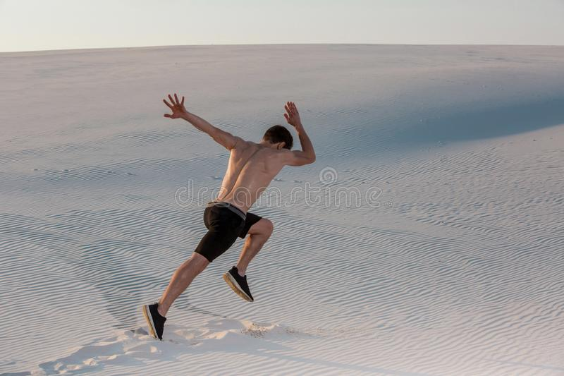 Geeigneter Mann, der schnell auf dem Sand läuft Starke Läuferausbildung im Freien auf Sommer stockfoto