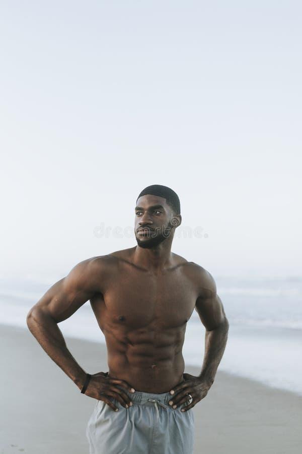 Geeigneter Mann, der am Strand aufwirft lizenzfreies stockbild