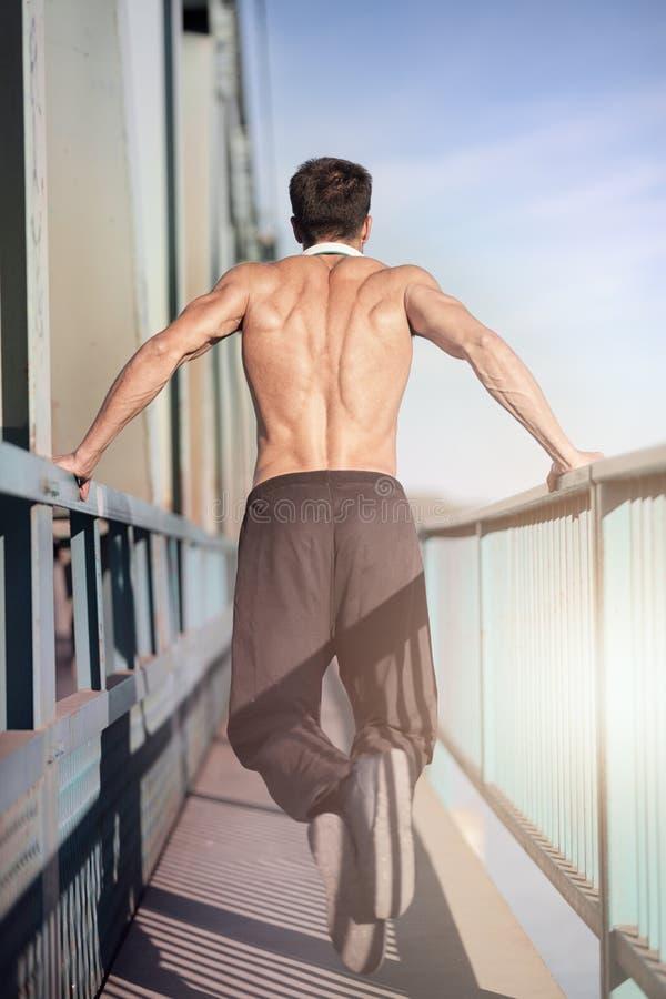 Geeigneter Mann, der Trizepsbadübung tut stockfotos