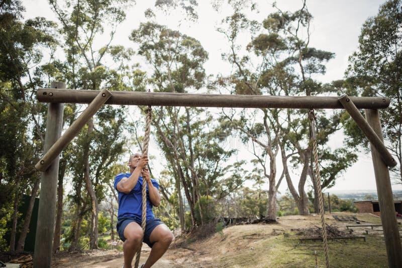 Geeigneter Mann, der unten das Seil während des Hindernislaufs klettert stockfotografie