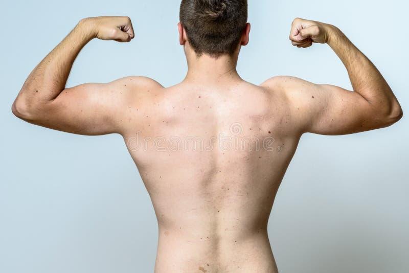 Geeigneter muskulöser junger Mann, der seine Muskeln biegt stockfotos