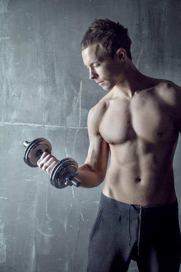 Geeigneter sportiver muskulöser Mann mit Stummglocke in der Hand stockfotos