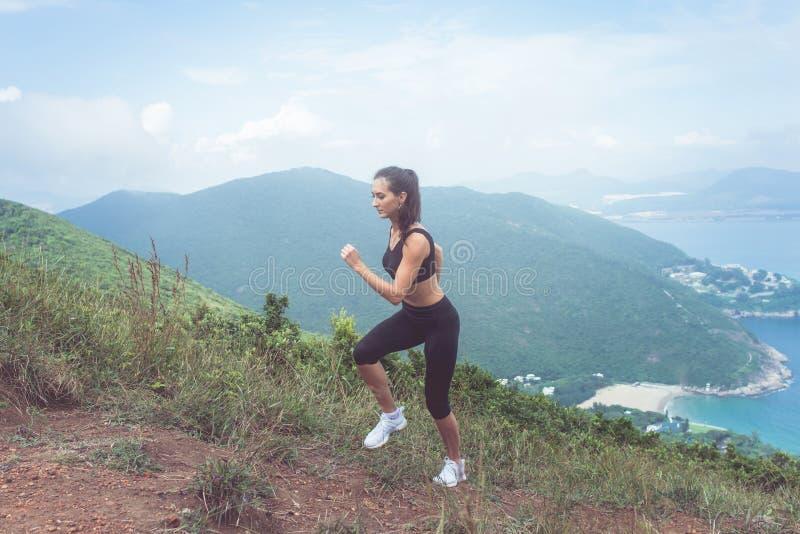 Geeigneter weiblicher Rüttler, der, aufwärts laufend mit Meer und Bergen im Hintergrund trainiert lizenzfreie stockfotografie