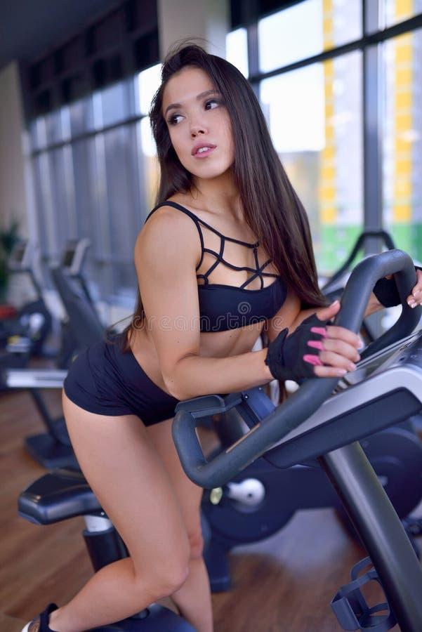Geeignetes Frauenhandeln Herz auf Fahrradtrainer in einer Turnhalle Eignungs-, Sport- und Lebensstilkonzept lizenzfreie stockfotos