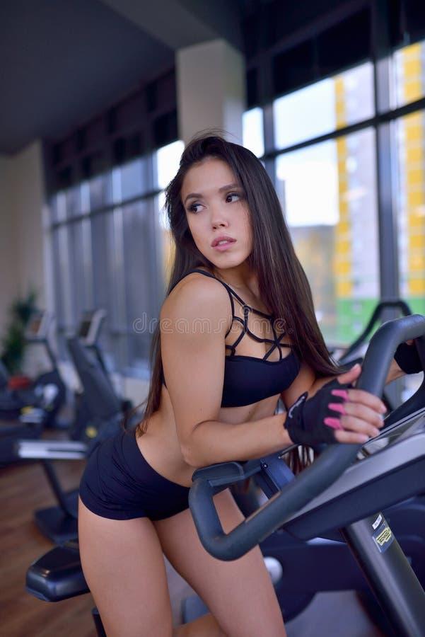 Geeignetes Frauenhandeln Herz auf Fahrradtrainer in einer Turnhalle Eignungs-, Sport- und Lebensstilkonzept stockfoto