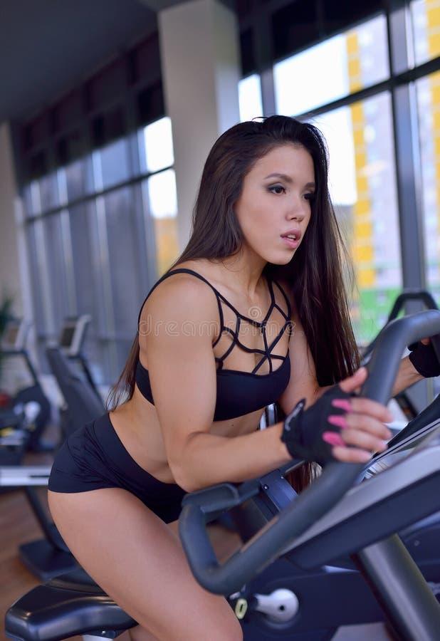 Geeignetes Frauenhandeln Herz auf Fahrradtrainer in einer Turnhalle Eignungs-, Sport- und Lebensstilkonzept lizenzfreies stockfoto